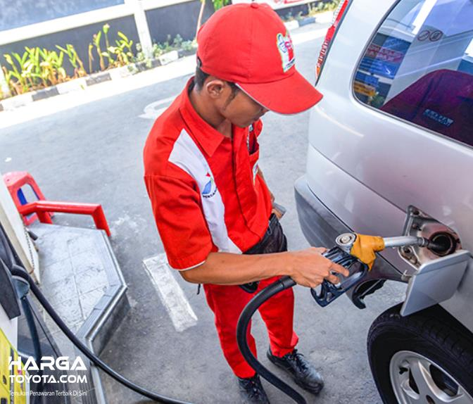 Gambar ini menunjukka n petugas SPBU isi bahan bakar mobil
