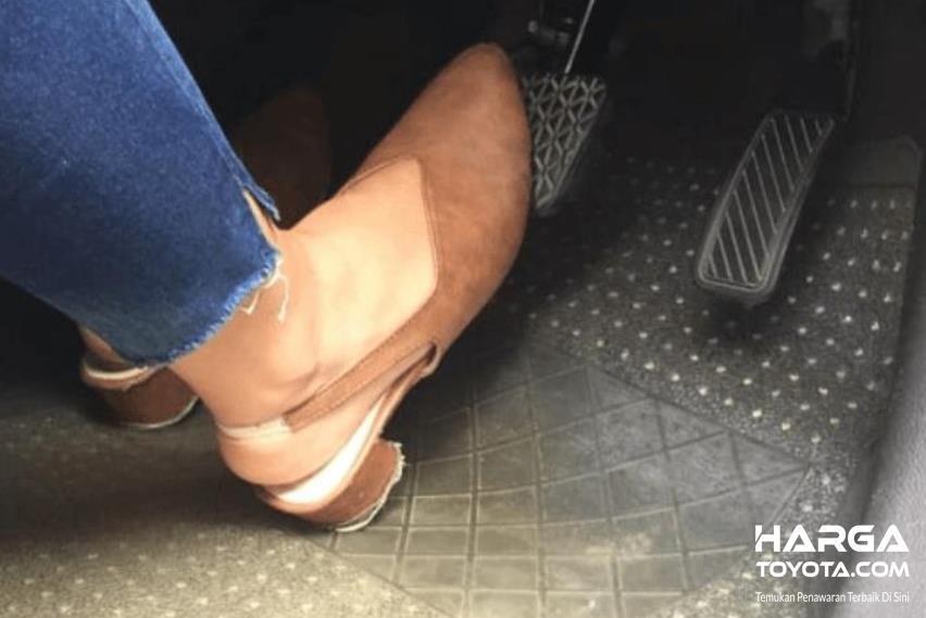 Gambar ini menunjukkan kaki menekan pedal rem