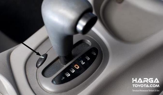 Gambar ini menunjukkan tuas transmisi dengan tombol