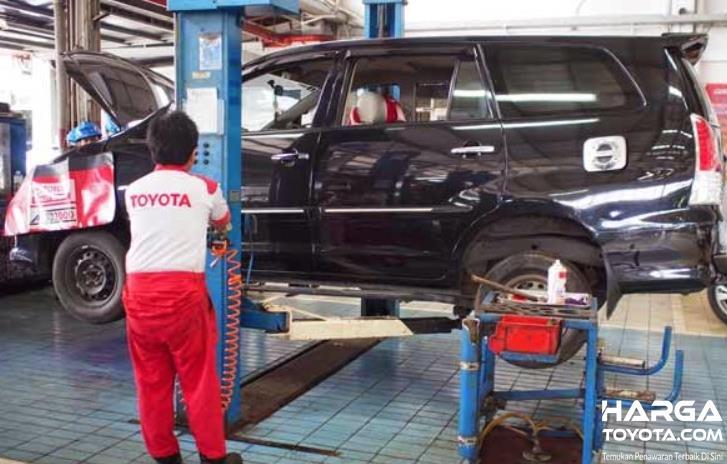 Gambar ini menunjukkan mekanik Toyota sedang melakukan perawatan pada mobil warna hitam