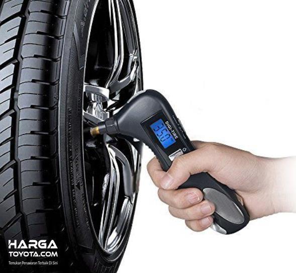 Gambar ini menunjukkan sebuah tangan memegang alat pengukur ban mobil