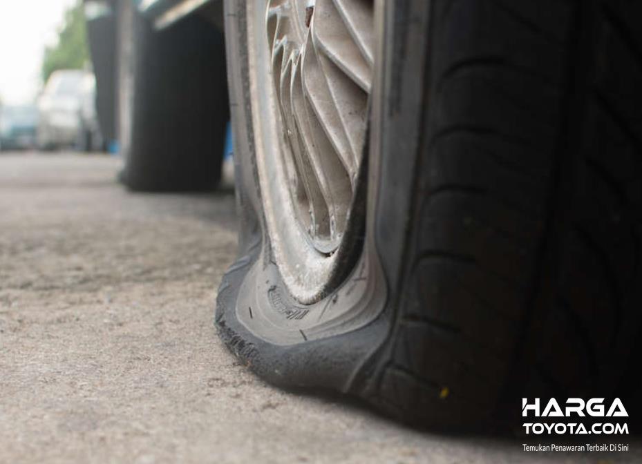 Gambar ini menunjukkan ban mobil dalam kondisi kempes