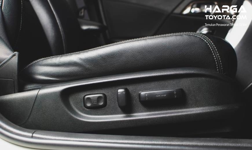 Gambar ini menunjukkan sebuah tangan sedang memegang alat pengatur jok mobil