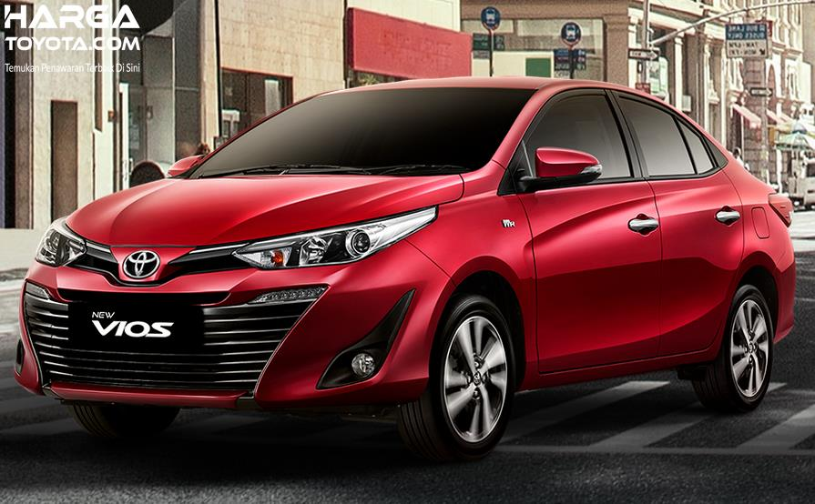 Gambar ini menunjukkan mobil sedan Toyota Vios merah tampak depan