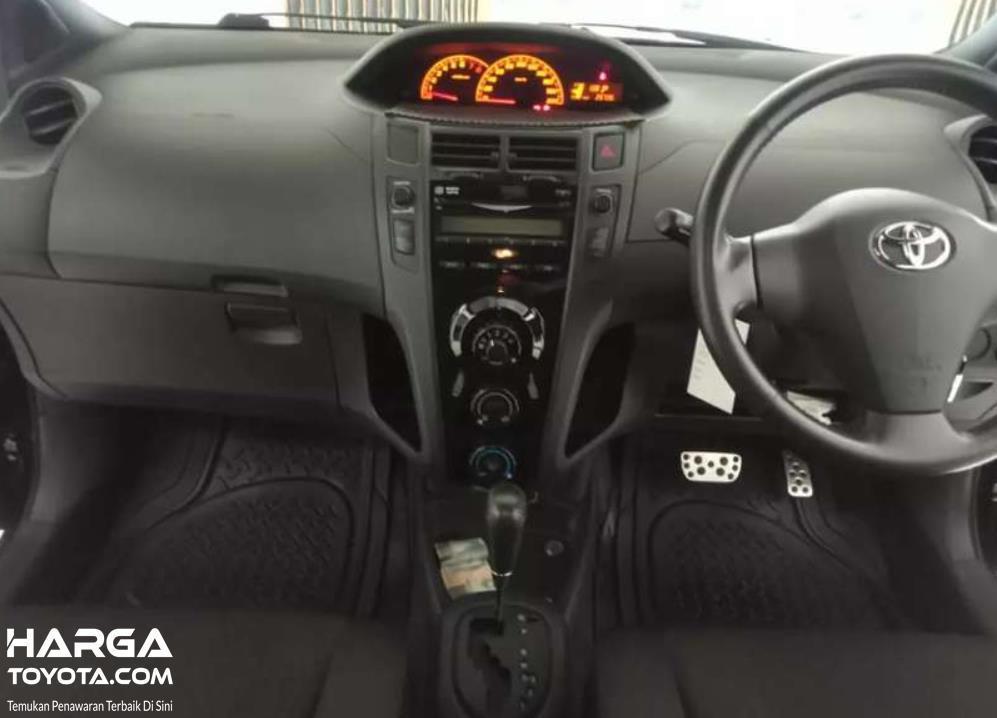Gambar ini menunjukkan tuas transmisi dan dashboard Toyota Yaris Generasi Pertama